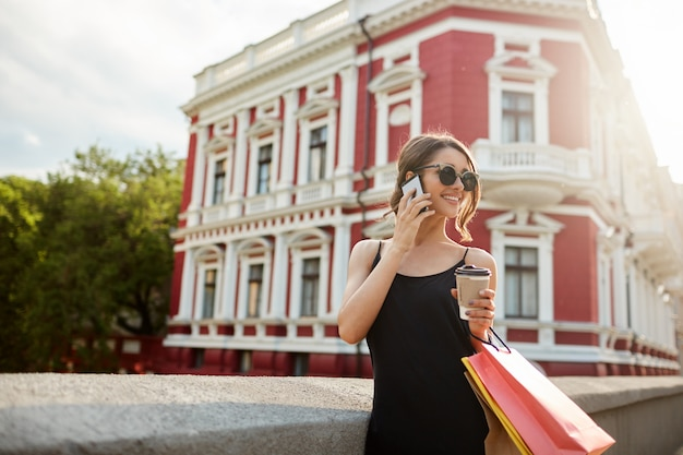 Pretty woman walking down the street. young attractive feminine girl smiling, walking near red building, looking aside with cheerful expression, holding bags in hands, being happy after successful sho