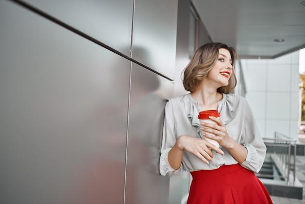 赤いスカートの屋外ライフスタイルを歩くきれいな女性
