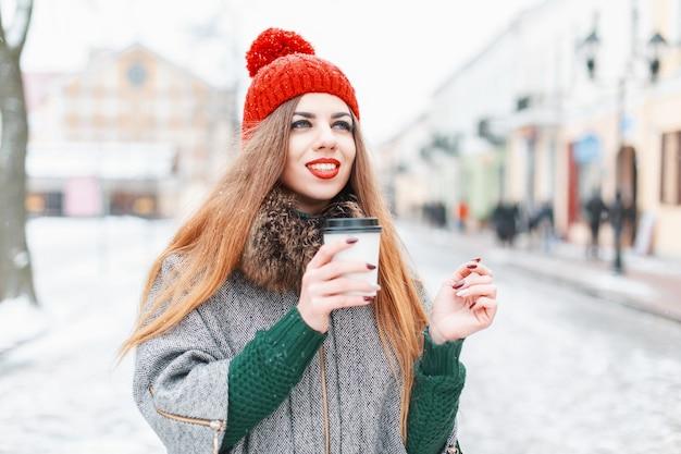 Красивая женщина гуляет по городу, пьет горячий напиток в зимний день