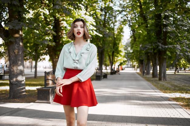 屋外の赤いスカートで公園を歩いているきれいな女性