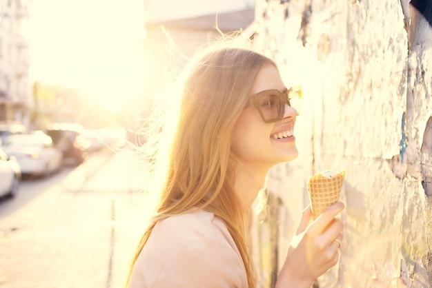 夏にアイスクリームを持って外を歩くきれいな女性