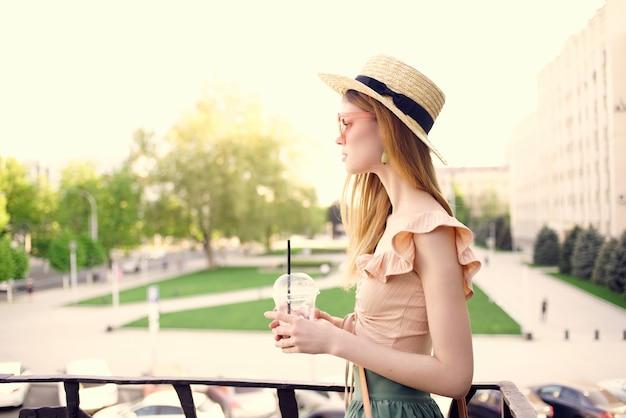 きれいな女性が飲み物の夏と屋外の公園を歩く