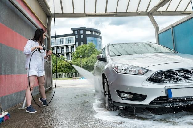 예쁜 여자 세척 및 거품과 압력으로 자동차 청소. 청소 또는 관리 차에 대한 개념입니다.