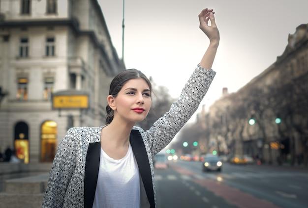 Pretty woman waving in the city