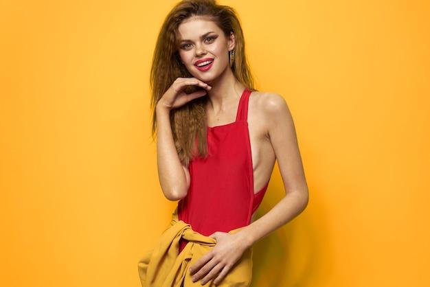 Pretty woman wavy hair red tank top fashion lifestyle cosmetics yellow background