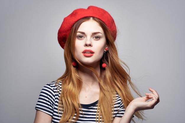 明るい背景のポーズをとって赤い帽子メイクフランスヨーロッパファッションを身に着けているきれいな女性