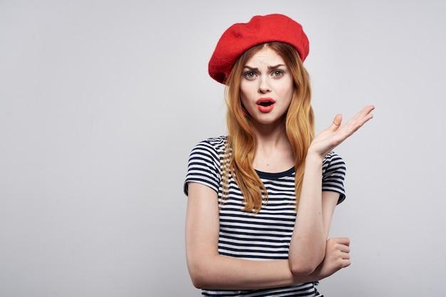 赤い帽子の化粧をしているきれいな女性フランスヨーロッパファッションポーズモデルスタジオ。高品質の写真