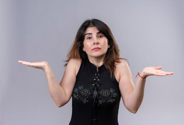 Bella donna che indossa una camicetta nera confusa non sa cosa fare