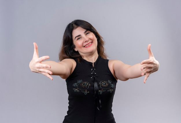 Bella donna che indossa una camicetta nera che abbraccia coridalmente con le braccia alla telecamera gioire su sfondo grigio