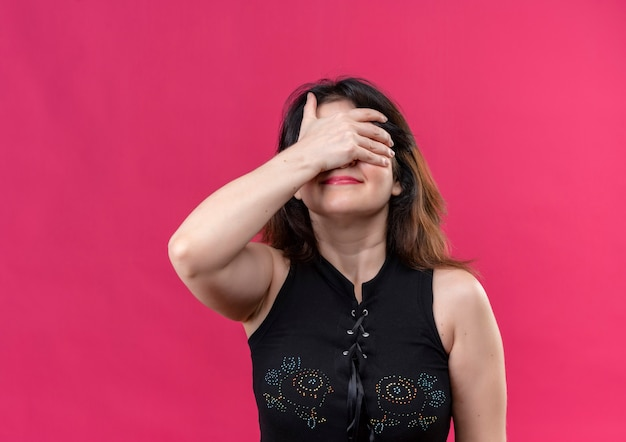 Pretty woman wearing black blouse doing happy facepalm over pink background
