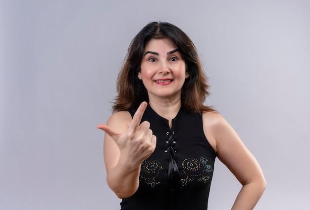 灰色の背景の上に幸せな人差し指をやって黒いブラウスを着ているきれいな女性