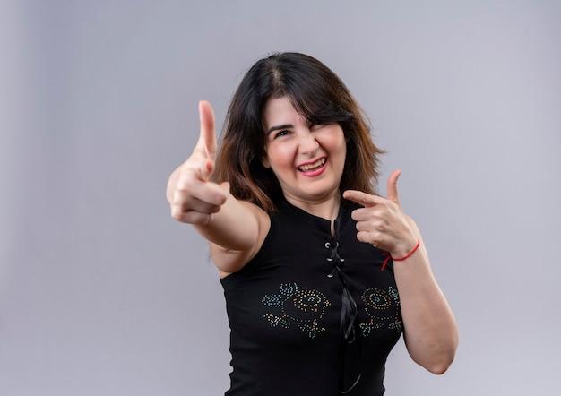 Красивая женщина в черной блузке с радостью делает тебе лучший знак