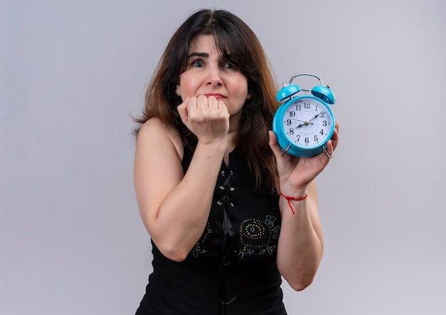 Pretty woman wearing black blouse holding clock scared of being late over gray background