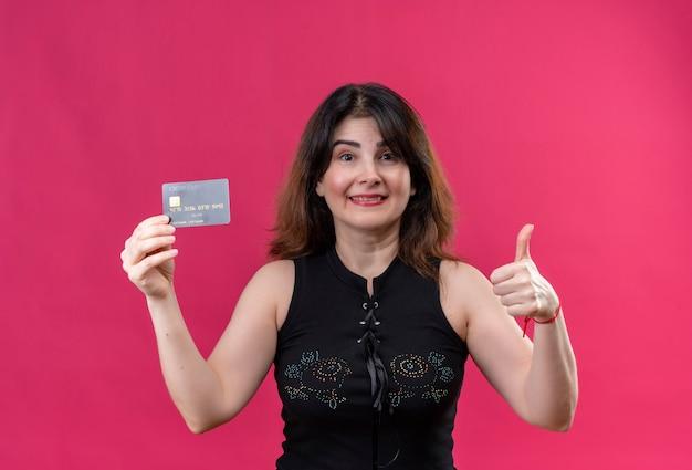 ピンクの背景の上にカードが好きな黒のブラウスを着ているきれいな女性