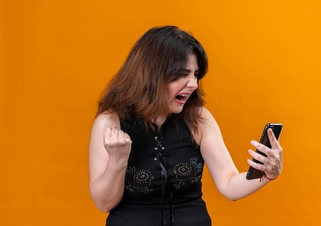オレンジ色の背景の上の電話で怒って見ている黒いブラウスを着ているきれいな女性