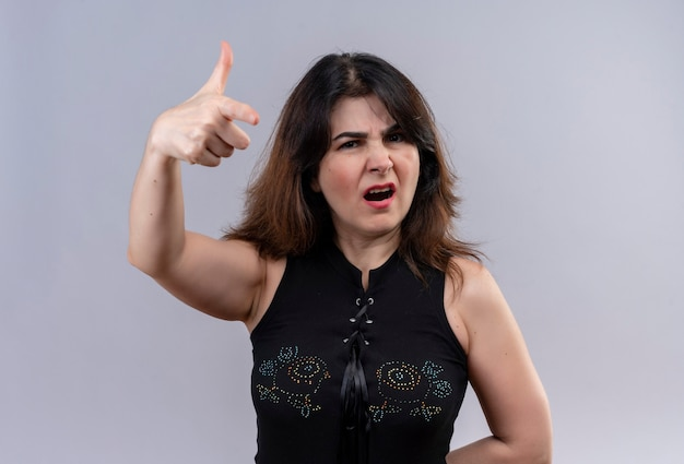 Pretty woman wearing black blouse looking arrogancy pointing with forefinger over gray background