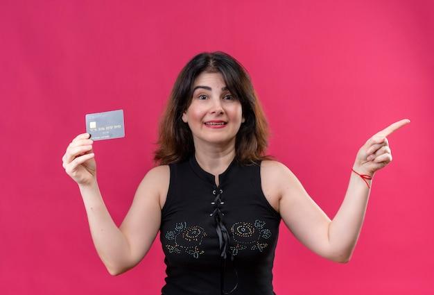 左向きのカードを持って幸せそうに見える黒いブラウスを着たきれいな女性