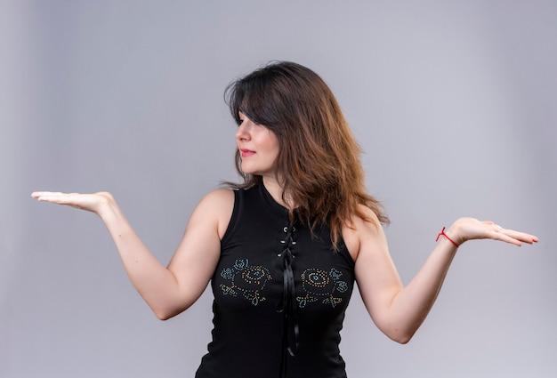 Bella donna che indossa una camicetta nera guardando a destra ha aperto le braccia