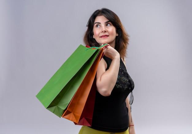 Bella donna che indossa una camicetta nera che sembra maestoso tenendo i sacchetti della spesa