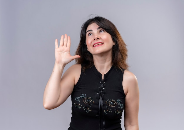 Pretty woman wearing black blouse looking up calling someone with hand