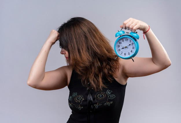 Pretty woman wearing black blouse looking upset for being late holding clock