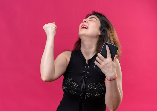 Bella donna che indossa una camicetta nera esulta con il telefono in mano