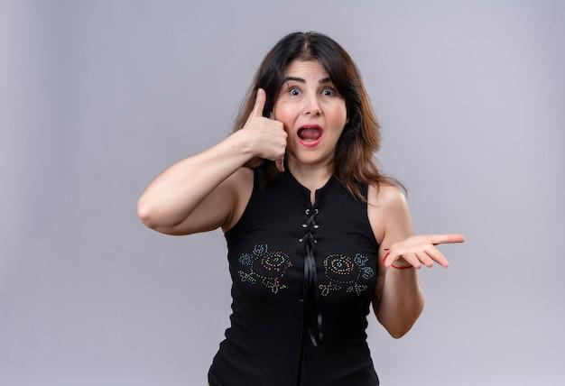 Bella donna che indossa una camicetta nera spaventata chiedendo di chiamare con le braccia