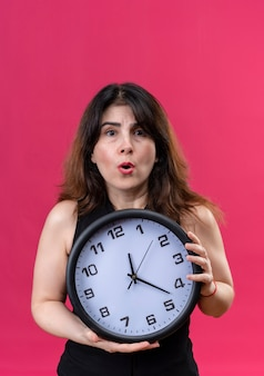 Pretty woman wearing black blouse scared for being late behind the clock