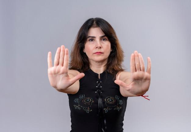 Красивая женщина в черной блузке серьезно показывает знак остановки руками