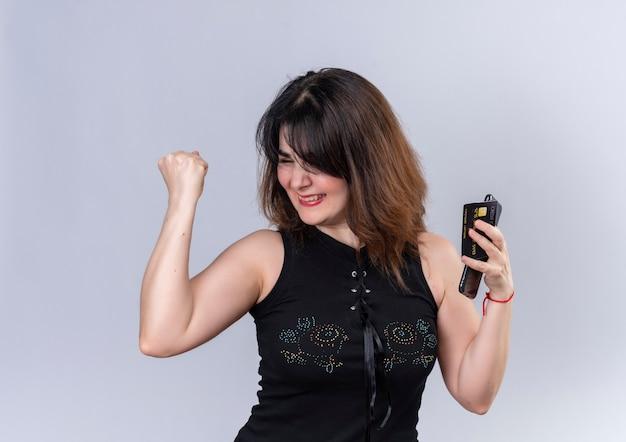 幸せを示す黒いブラウスを着たきれいな女性は、携帯電話とカードを持って署名しました