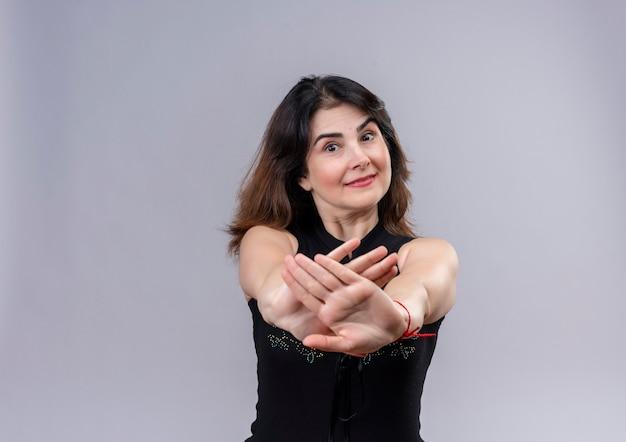 Bella donna che indossa camicetta nera che non mostra alcun segno con le mani