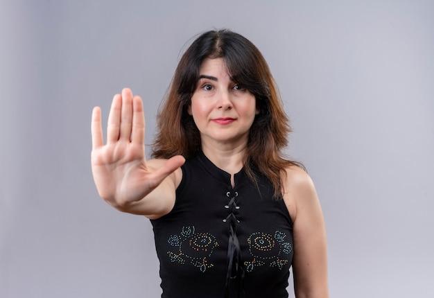 Красивая женщина в черной блузке показывает знак остановки правой рукой