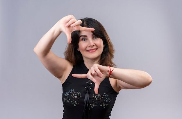 指でフレームをキャッチ笑顔の黒いブラウスを着ているきれいな女性