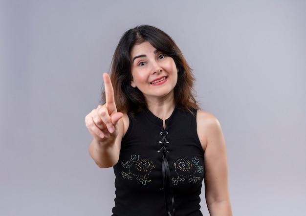 Bella donna che indossa camicetta nera sorridente mostrando il divieto con l'indice