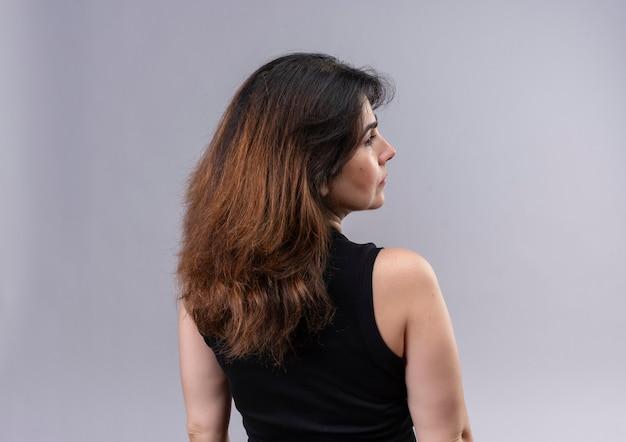 Bella donna che indossa una camicetta nera voltandole le spalle