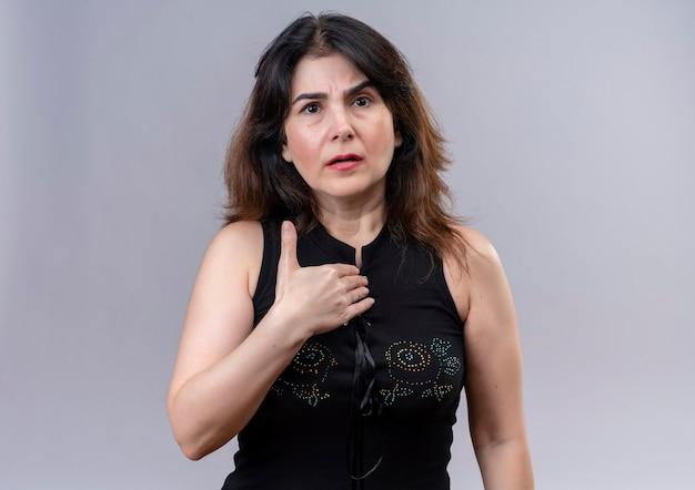 ポグレーの背景の上に立っている自分自身に非難された顔のポイントで黒いブラウスを着ているきれいな女性