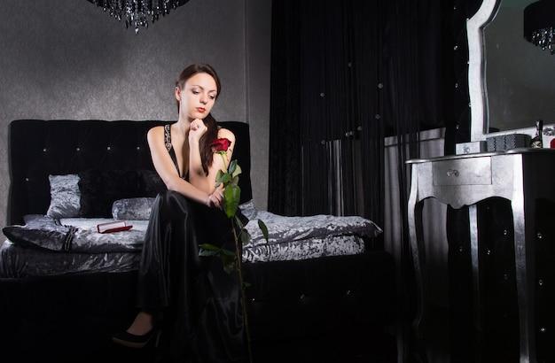 Симпатичная женщина в черном платье, держащая цветок розы, ожидая чего-то в спальне.