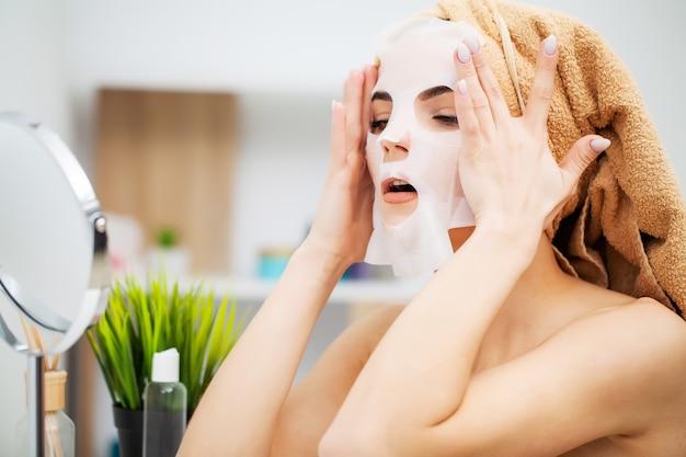 自宅で顔のケアマスクを着てきれいな女性