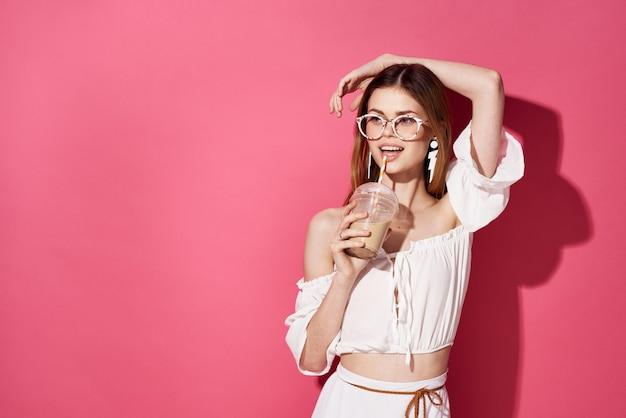Красивая женщина в очках украшение очарование напитка в руках роскошное розовое пространство