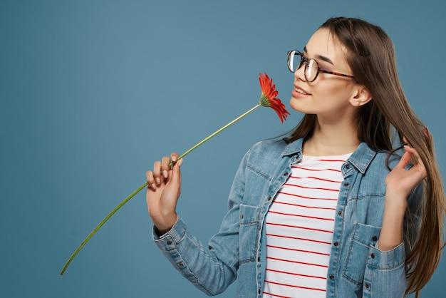 眼鏡をかけているきれいな女性赤い花夏スタイル青い背景