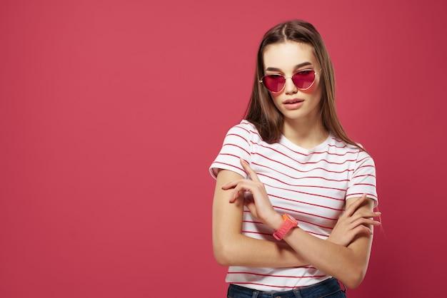 분홍색 배경에 포즈를 취하는 안경 줄무늬 티셔츠 스타일을 입은 예쁜 여자
