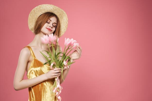 帽子の花束の花の装飾の魅力ピンクの背景を身に着けているきれいな女性