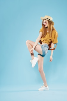 帽子のファッションを身に着けているきれいな女性は、若者のスタイルの青い背景をポーズします