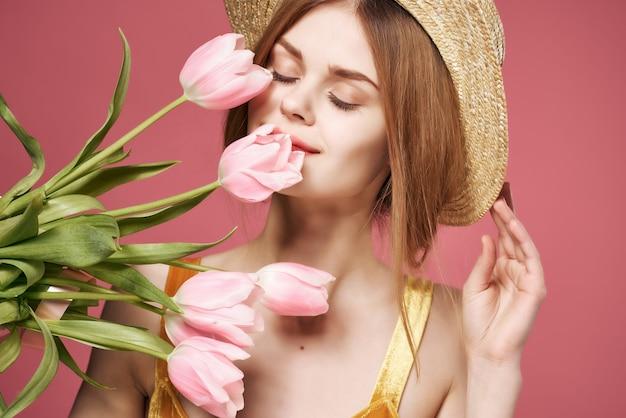 帽子をかぶったきれいな女性ピンクの花花束グラマークローズアップ