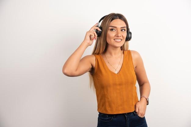 白い背景の上のヘッドフォンを身に着けているきれいな女性。
