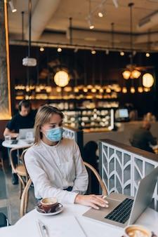 Красивая женщина в медицинской маске, используя ноутбук для работы