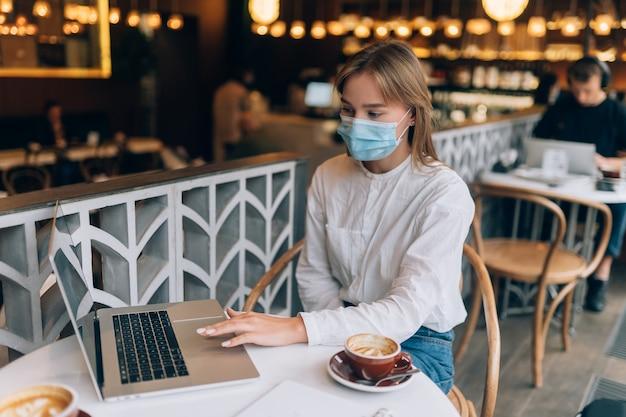 작업에 노트북을 사용 하여 의료 얼굴 마스크를 쓰고 예쁜 여자