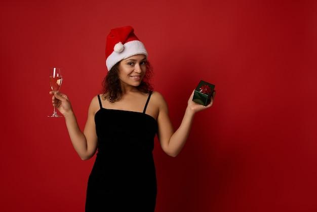 산타 모자와 검은 벨벳 드레스를 입은 예쁜 여성은 샴페인 플루트와 스파클링 와인, 선물 상자를 들고 빨간색 배경에 포즈를 취한 이빨 미소, 복사 공간을 들고 있습니다. 크리스마스, 새해 복 많이 받으세요