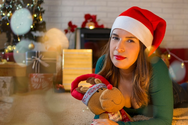Pretty woman, wearing a santa hat, lying on the carpet of her house with a stuffed animal and christmas decoration.