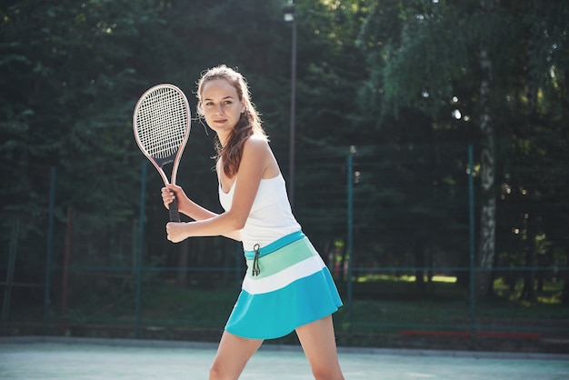 A pretty woman wearing a sportswear tennis court on the court.